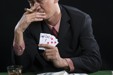 The gambler is smoking for stress relief when he defeat in poker game