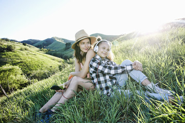 Mother and daughter sitting on hill listening to headphones