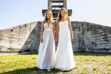 Lesbian brides holding hands in grass near concrete structure