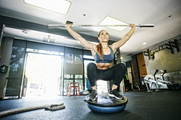 Mixed Race woman balancing with barbell in gymnasium
