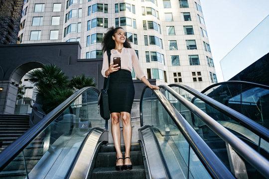 Smiling Hispanic businesswoman riding escalator outdoors