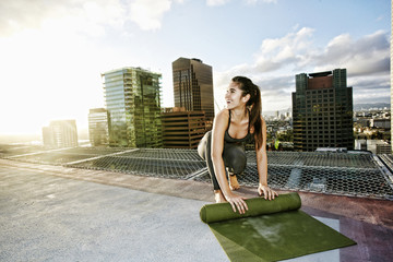 Caucasian woman rolling exercise mat on urban rooftop after yoga