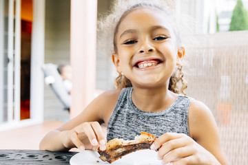 Smiling Mixed Race girl eating rib outdoors