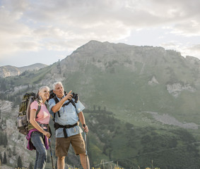 Caucasian couple with binoculars hiking on mountain