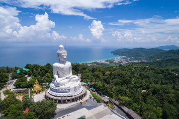 White buddha statue on top of the mountain with blue sky in Phuket