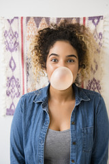 Mixed Race woman blowing bubble with gum