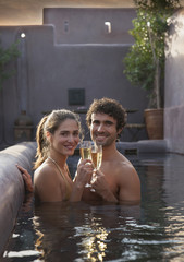 Smiling Caucasian couple toasting with champagne in swimming pool