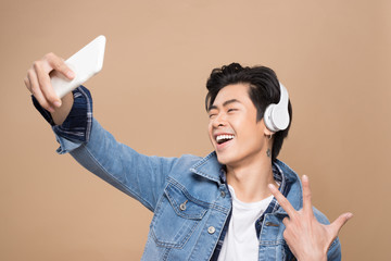 Portrait of a young asian handsome man with headphones smiling and listening to music