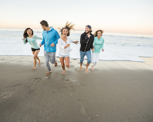 Smiling friends running on beach