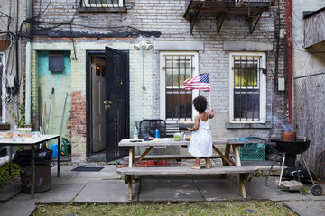 Mixed Race girl standing on backyard bench waving American flag