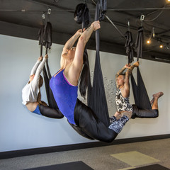 People performing yoga hanging from silks