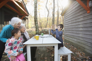 Grandson photographing grandmothers and sister with digital tablet