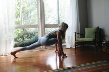 Caucasian woman stretching leg on floor