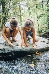 Mixed Race girls kneeling on rock looking at stream