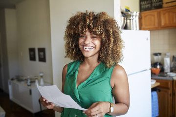 Smiling Black woman holding paperwork