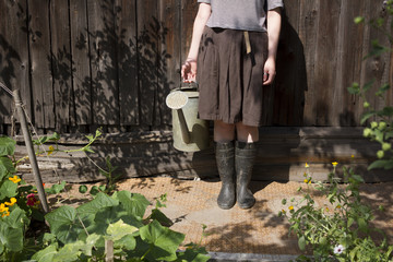 Caucasian woman holding watering can in garden