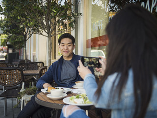 Woman taking picture of man while sitting at restaurant