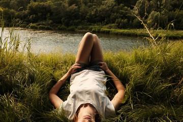 Caucasian woman laying near river