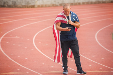 Caucasian man wearing American flag as cape on track texting on cell phone