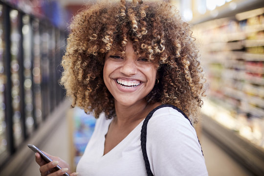 Black woman holding cell phone smiling in grocery store
