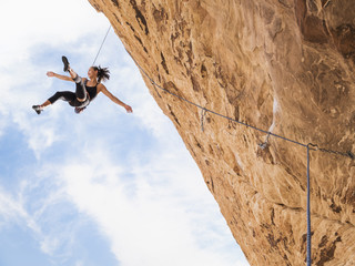 Mixed Race girl hanging from rope while rock climbing