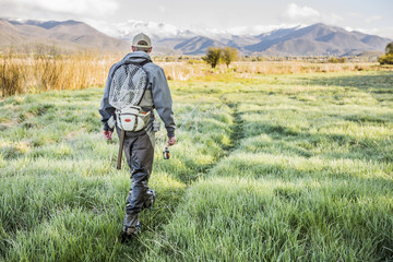 Caucasian man carrying fishing rod in field