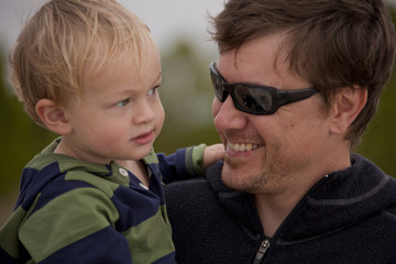 Caucasian father wearing sunglasses holding son