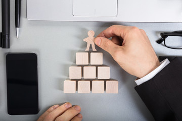 Businessperson Arranging Human Figure Cut Out On Wooden Blocks