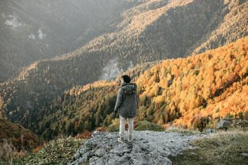 Caucasian man standing on mountain rock overlooking valley