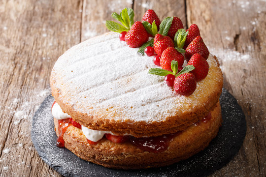 Home Victoria sponge cake, decorated with strawberries and mint closeup. Horizontal