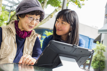 Older Japanese mother and daughter using digital tablet