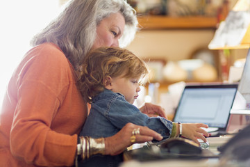 Caucasian baby boy in lap of grandmother using computer