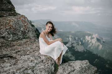Smiling Caucasian woman sitting on rock overlooking landscape