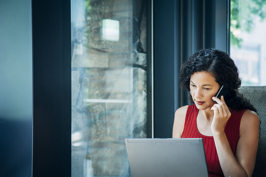 Mixed Race woman using laptop and cell phone in armchair