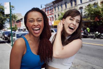 Friends laughing on city sidewalk