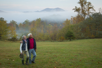 Older Caucasian couple walking in field