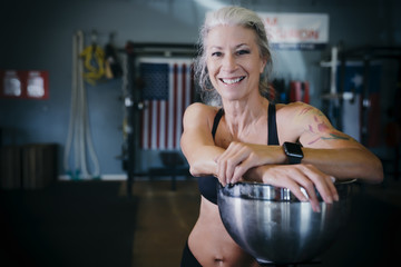 Smiling Caucasian woman leaning on bowl in gymnasium