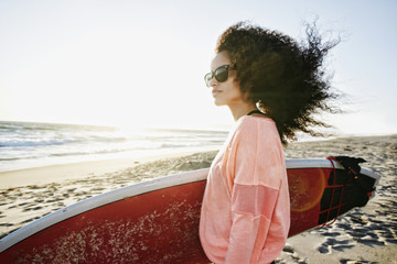 Hispanic woman holding surfboard at beach