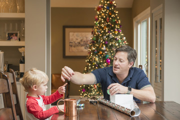 Caucasian fathers and son wrapping Christmas gift