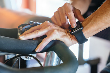 Caucasian woman tapping smart watch on stationary bicycle
