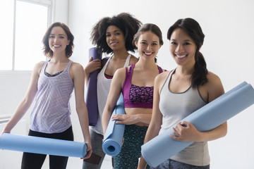 Smiling women holding rolled up exercise mats