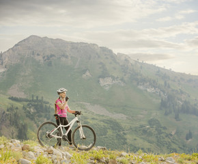 Caucasian woman with mountain bike drinking from backpack