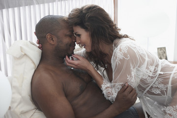 Woman caressing face of man in bed