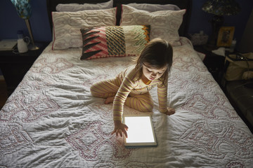 Mixed Race girl using digital tablet on bed