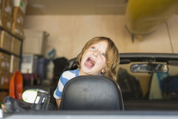 Caucasian boy making a face in convertible car