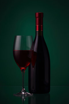 Bottle of red wine and glass on green