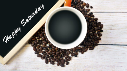 Heat a cup of coffee, coffee beans and a whiteboard with the word HAPPY SATURDAY