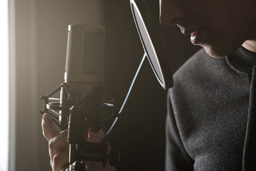 Closeup of lips and hands on a microphone of a young man standing in profile in the rays of the sun