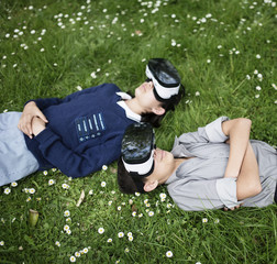 Mixed Race brother and sister laying in grass wearing virtual reality goggles