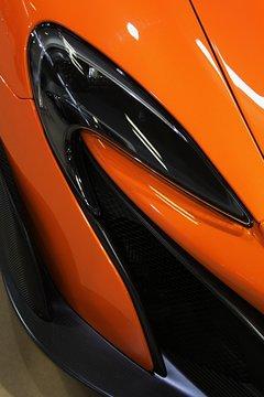 Detail of elegant shaped headlight on modern luxurious english sport car.